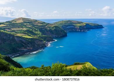 Vue depuis le Miradouro de Santa Iria sur l'île de São Miguel dans les Açores. La vue montre une partie du littoral nord avec des falaises et des champs verts au sommet de la falaise.