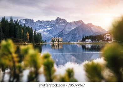 View of Misurina lake with large building of Institute Pius XII through bushes at sunset. Dolomites, Italy.