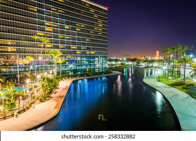 View of a modern building and Rainbow Lagoon Park at night, in Long Beach, California.