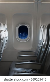 View of modern city skyline at night in an airplane window with airplane seats on the front