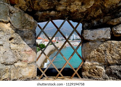 View of the modern city through the rusty bars of the battlements of the old fortress.