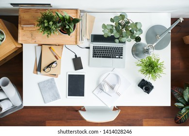 View of modern employee workplace with gadgets, green plants, lamp, photocamera, copybooks, pens, eyeglasses and headphones
