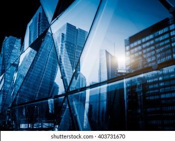 Blick auf einen modernen Wolkenkratzer aus Glas, der die umliegenden Gebäude reflektiert, blaues Bild.