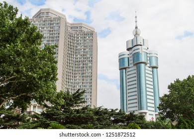 view of modern high-rise buildings from the city Park of the Chinese city of Dalian. green trees with skyscrapers in the background. Travel in China. Dalian, China - august 12, 2018