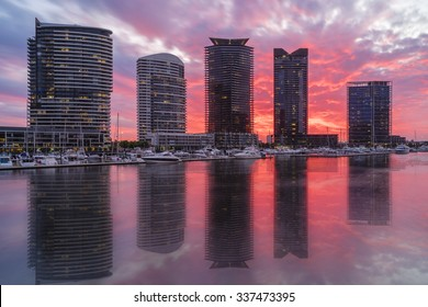 View of modern luxurious apartments and marina in Docklands, Melbourne with reflection during sunset.