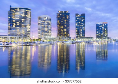 View of modern luxurious apartments and marina in Docklands, Melbourne with reflection during twilight.