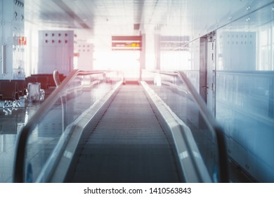 View of a modern travelator stretching into the vanishing point indoors of a railways station depot; moving walkway inside of a departure area of an airport terminal with a reddish flare at the end