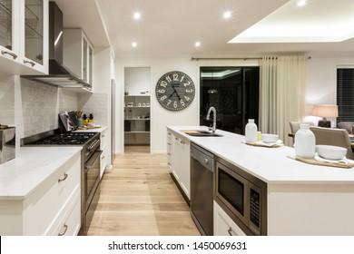 Der Blick auf die moderne Küche mit Kücheninsel, Schränken, Parkettboden und Küchenablage im Hintergrund.