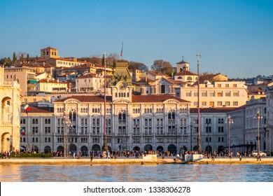 View from Molo Audace to main square Piazza Unita d Italia and hill with castle Castello di San Giusto on sunset in Trieste, Italy