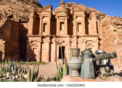 View of the Monastery in the Ancient City of Petra, with antique metal vases and tea kettles in the foreground - Jordan- Jordan