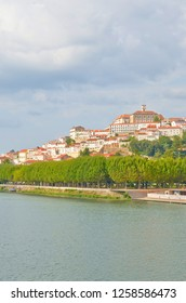 View of Mondego River along the portuguese city of Coimbra during cloudy summer afternoon. The dominant of the city is the bell tower belonging to the famous University of Coimbra. Sep 4th 2018