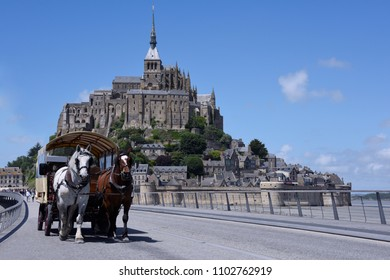 View of Mont Saint Michel, and a horse carriage crosses. France