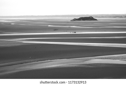View from Mont Saint Michel (one of most popular landmarks in France). Groups of people seen far away walking on the ocean bottom during low tide. Black and white photo.