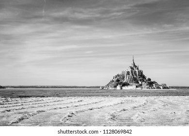 View of the Mont Saint-Michel tidal island, situated in France on the border between Normandy and Brittany, with hay windrows drying in a field in the foreground under a blue sky with fibrous clouds.
