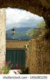 View of the Mont Ventoux through a porch of the village of Faucon. Ventoux mountain. In the foreground a street light, a door, flowers, a tree, a facade. Spring in France, Provence, Vaucluse.