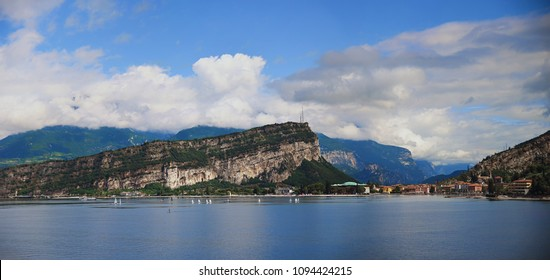 view to monte brione and torbole, lake garda with sailboats, and blue cloudy sky