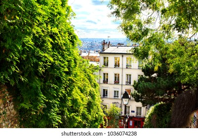 View from the Montmartre hill in Paris - one of the side streets downhill descending between walls covered with a green lush foliage