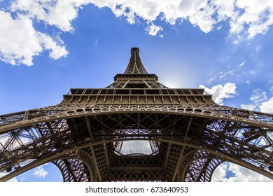 View of monumental Eiffel tower from below with clear blue sky with some clouds