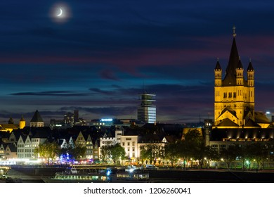View to the Moon above the beautiful illuminated River Rhine a big Curch, modern Building and Ships at Night in Cologne Germany in 2018.