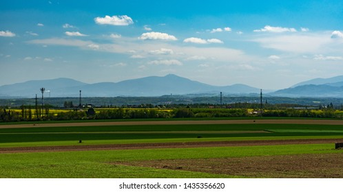 view to Moravskoslezske Beskydy mountain range with highest Lysa hora hill from field above Ostrava-Poruba city in Czech republic during nice springtime day