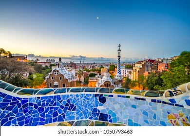 View of mosaic tile and Barcelona cityscape in famous park Guell at summer sunset , Spain