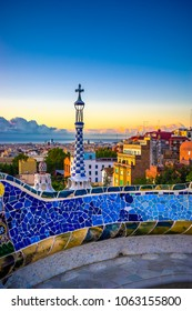 View of mosaic tile in Summer Park Guell and Barcelona cityscape in the background, Spain