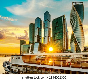 View of Moscow international business center (Moscow city) and pleasure boat against the setting sun, Russia