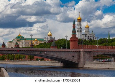 View of the Moscow Kremlin and a large stone bridge against a cloudy sky