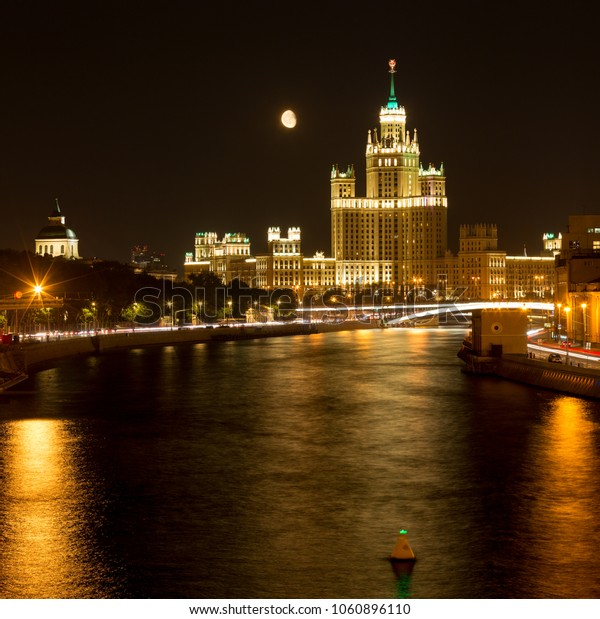 View of Moskva River with lightship, Bolshoy Krashokholmsky Bridge and embankment colorfully illuminated in moonl