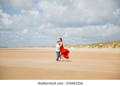 View of mother and her son who stand in embrace on the beach