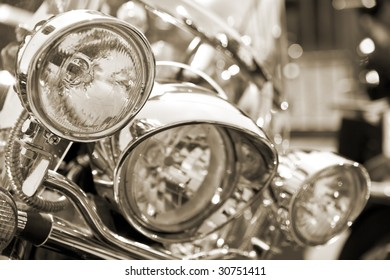 View of motorbike front head lamps. Sepia tone. Shallow DOF.