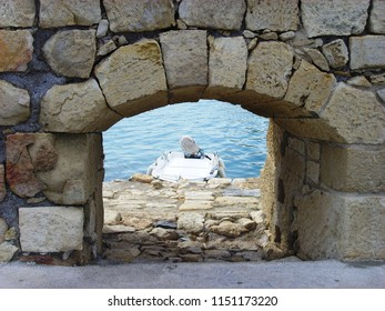View of a motorboat in the port through a loophole (stone arch), at the fortress of Koules, the Venetian castle of Heraklion, Crete