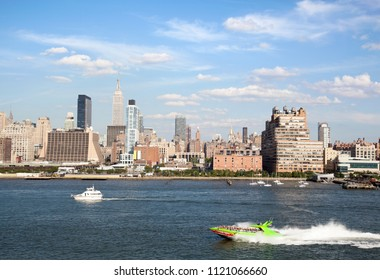 The view of motorboats passing by along Hudson River and Manhattan Midtown skyline in a background (New York City).