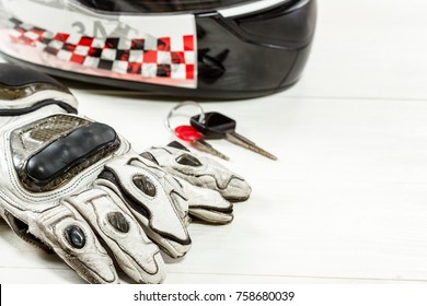 View of motorcycle rider accessories. Items included motorcycle helmet, gloves and keys. Motorcycle travel dream concept.