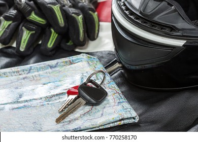 View of motorcycle rider accessories. Items included motorcycle helmet, gloves, keys, map and jacket. Motorcycle travel dream concept.