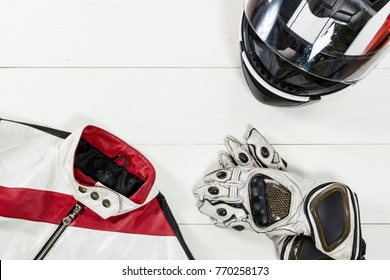View of motorcycle rider accessories. Items included motorcycle helmet, gloves and jacket. Motorcycle travel dream concept.