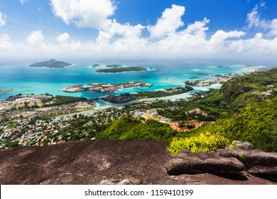 View from Mount Copolia over the east of Mahe, Seychelles with the capital Victoria and Eden Island, granite rock in the foreground.
