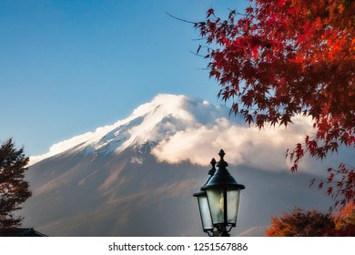 View Of Mount Fuji with cloud cover and a maple tree in autumn and a street lamp in the foreground from Fujikawagichiko, a resort town in Japan.