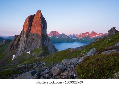 View from Mount Hesten on Iconic Mountain Segla in light of midnightsun in front of clear sky and mountain range in background, rocks and boulders in foreground, Fjordgard, Senja, Norway