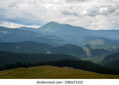 View of Mount Petros from Kukul meadow with fir wood and shepherd houses on cloudy day. Wonderful nature scenery of Carpathian Mountains, Ukraine