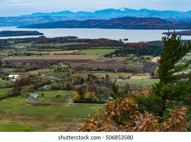 view from Mount Philo of rural Vermont farm valley in autumn  with Lake Champlain and the snow topped Adirondack Mountains  in distance