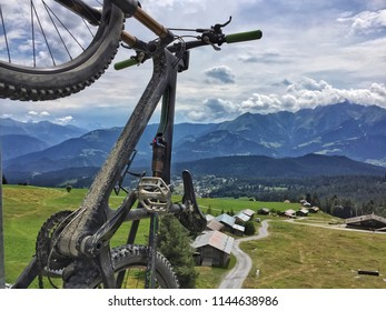 View of mountain bike hanging on ropeway chair with spectacular view of alpine mountains in Switzerland. Uphill ride for downhill action in Flims, Europe