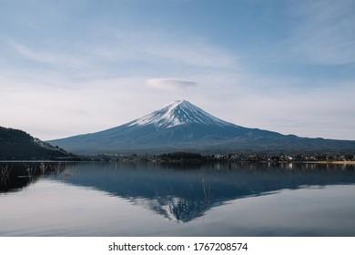 View of mountain Fuji with crown cloud and reflection on smooth water at Kawaguchiko lake.