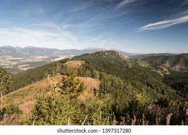 view from mountain glade bellow Slema hill in autumn Nizke Tatry mountains in Slovakia with hills of Nizke Tatry mountains and peaks of part of Zapadne Tatry and Vysoke Tatry mountains