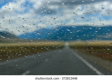 View of the mountain landscape with an asphalt road, mountains, sky and clouds through the window glass of the car covered by rain drops