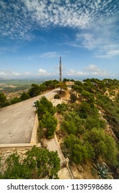 View from the mountain over the road to antenna tower on the foreground and the valley in summer day. There are spindrift clouds (Spain, Majorca, San Salvador)