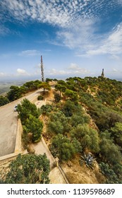 View from the mountain over the road to antenna tower and the statue of Jesus on the foreground and the valley in summer day. There are spindrift clouds (Spain, Majorca, San Salvador)