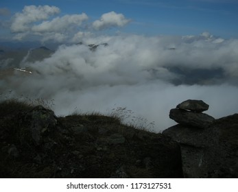 View from mountain range to the valley above fog and clouds, cairn , high altitude landscape,above clouds,fog. Mystique  relaxing  nature, blue sky, sunlight