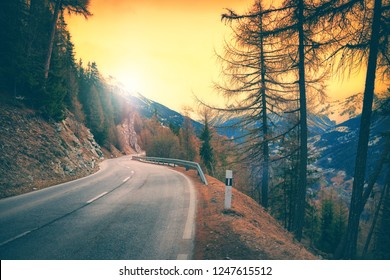 View of mountain road at sunset, Alps Switzerland. Winter nature background