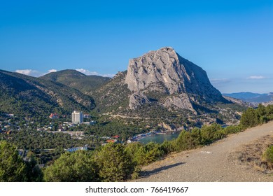 View from mountain stony path on thicket, marine town near Black sea bay and mountains above town in distance under clean blue sky in Crimea